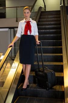 Hostess di volo con borsa trolley in piedi sulla scala mobile
