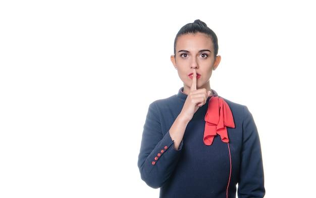 白い背景の上の静けさのジェスチャーをするスチュワーデスの女性。唇に指を持って