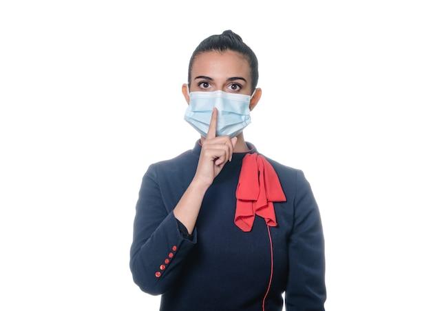 白い背景の上の静けさのジェスチャーをするフェイスマスクを持つスチュワーデスの女性。唇に指を持って