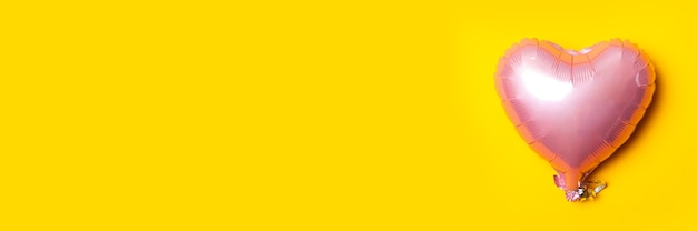 Air pink metal balloon in the form of a heart on a bright yellow background. flat lay, top view. banner.
