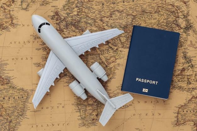 古い地図の飛行機とパスポート。旅行、冒険の概念