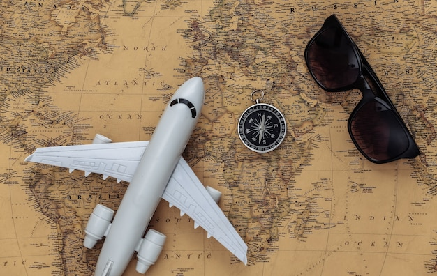 Air plane, compass and compass on old map. travel, adventure concept