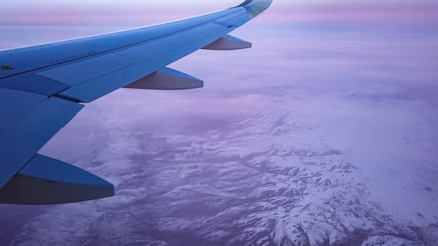 비행기는 눈 덮인 산 위로 구름 사이를 날아갑니다. 보라색 일몰, 항공기 창에서 날개의보기에 겨울 공중 풍경.