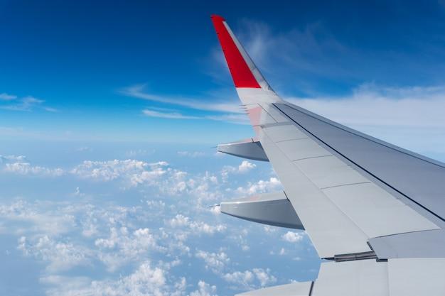푸른 하늘과 구름에 있는 비행기 날개는 항공 운송에 사용될 수 있으며 배경 여름 시즌 개념을 여행하기 위해 시즌을 엽니다.