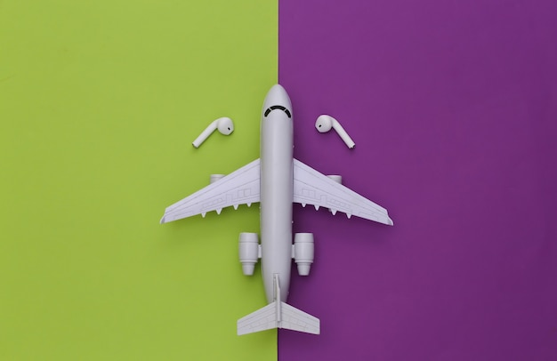 Air plane and wireless headphones on a purple-green background.