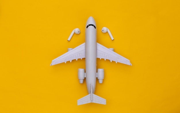Air plane and wireless headphones on yellow background.