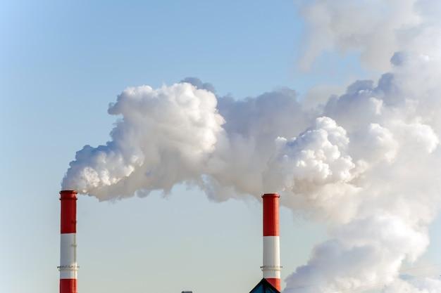 Загрязнение воздуха в городе. дым из трубы на голубом небе