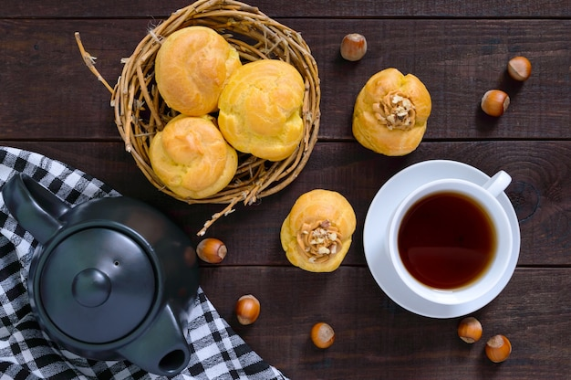 Воздушные профитроли с карамельным кремом и орехами, чашка чая, чайник