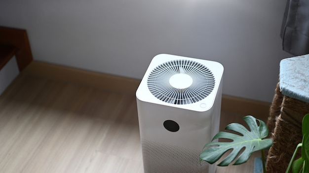 Air purifier in comfortable living room with house plant on the wooden floor.