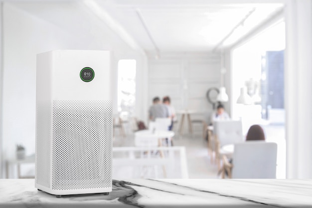 Air purifier in white workplace room with filter for cleaner removing fine dust