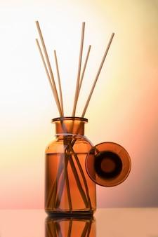 空気清涼飲料ボトルモックアップ、ライトローズグラデーション背景にリードディフューザー。アロマセラピーのコンセプトです。ホームフレグランスボトル