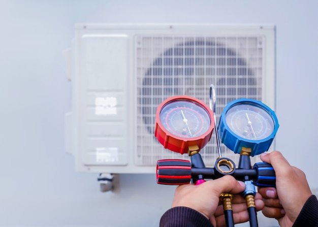 Air repair mechanic using measuring equipment for filling industrial factory air conditioners