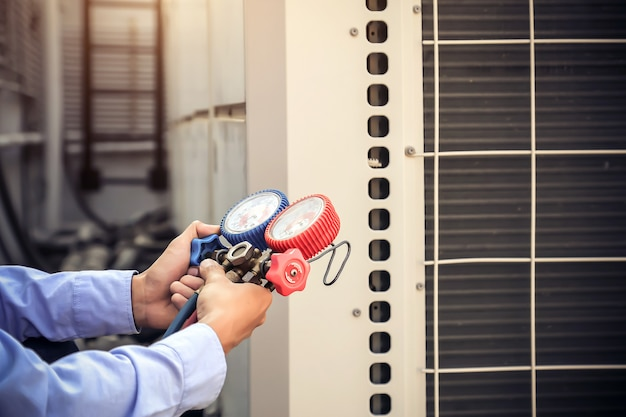 Ремонтник-механик с использованием измерительного оборудования для заправки промышленных заводских кондиционеров