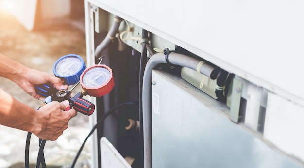 Слесарь по ремонту воздуха с использованием измерительного оборудования для заполнения промышленных заводских кондиционеров