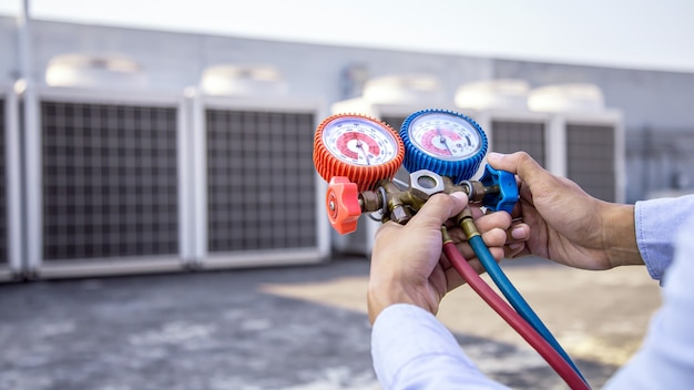 산업용 공장 에어컨을 채우기 위해 매니 폴드 게이지를 사용하는 공기 수리공