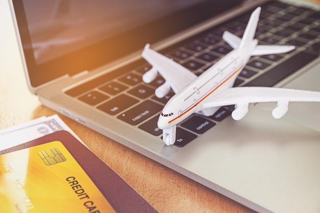 Авиабилеты, паспорта и кредитные карты возле портативного компьютера и самолета на столе. концепция онлайн-бронирования билетов