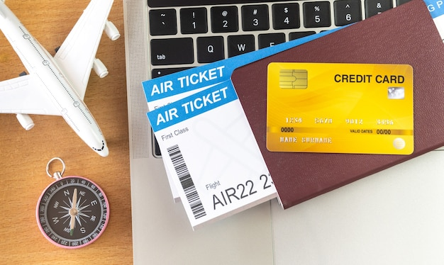 Air tickets and passports near laptop computer and airplane on table. online ticket booking concept