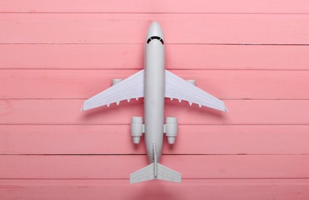 エアツーリズムまたはトラベルフラットレイ。ピンクの木の飛行機の置物