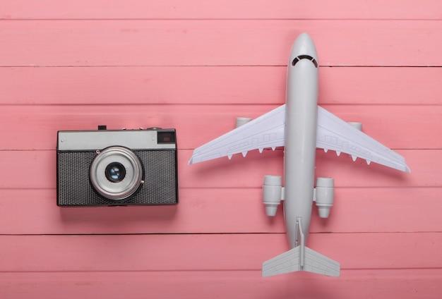 Воздушный туризм или путешествия по квартире. фигурка самолета с фотоаппаратом на розовом деревянном