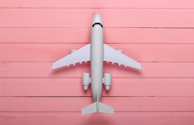 Air tourism or travel flat lay. airplane figurine on a pink wooden