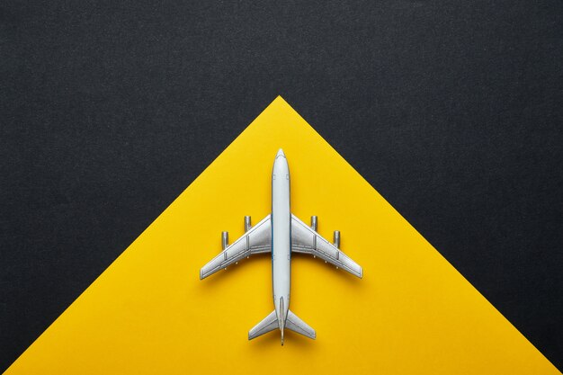 Air travel concept with airplane and yellow with black background with copy space and top view.