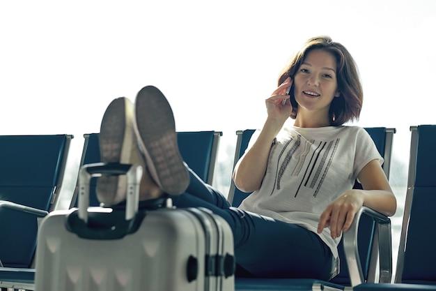 Концепция воздушного путешествия с молодой случайной девушкой, сидящей с чемоданом ручной клади. женщина аэропорта разговаривает по телефону у ворот, ожидающих в терминале.