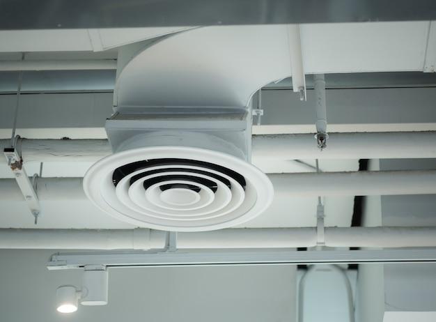 Вентиляционная труба установлена на потолке торгового центра или здания фабрики.