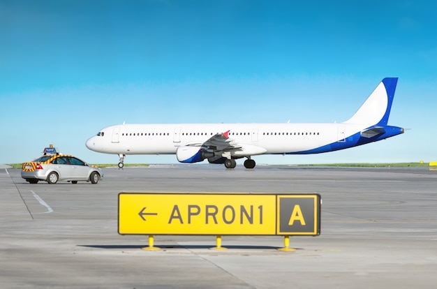 Aircraft at the airport after landing and the airport service car with the inscription follow me.