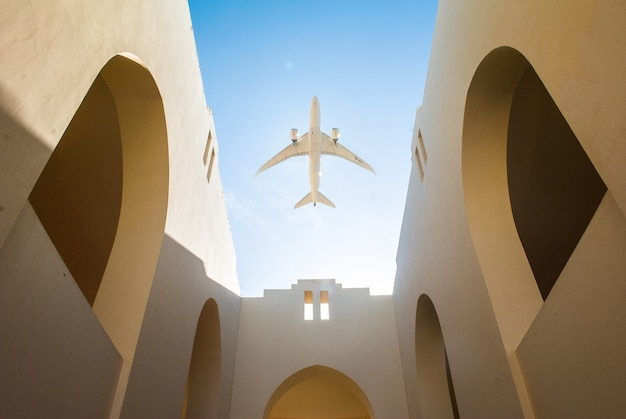 Aircraft over the arabic style yard of the house with white walls and clear blue sky