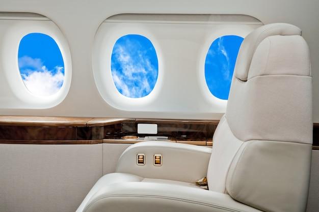 Интерьер самолета бизнес-класса с голубым небом за иллюминаторами