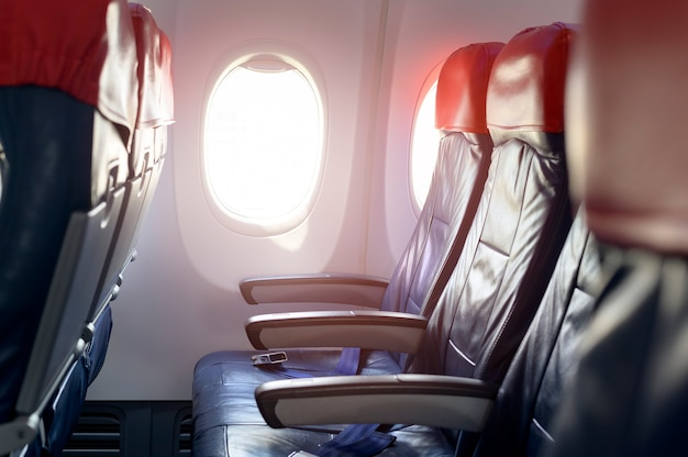 An aircraft cabin with empty passenger rows of seats.