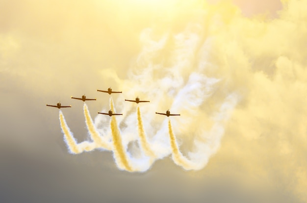 Aircraft fighter jets smoke the background of sky clouds and sun.