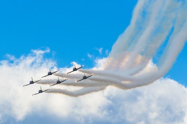 Самолеты-истребители курят на фоне голубого неба белые облака