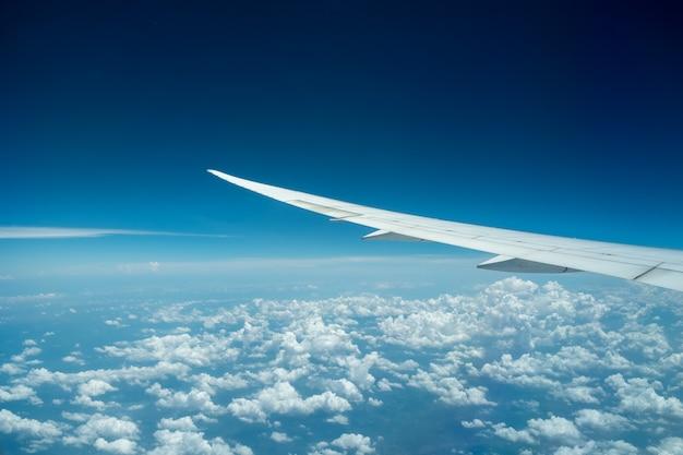 航空機は、曇り空と青い空の上を飛んでいます。飛行機の窓からの眺めはいい。
