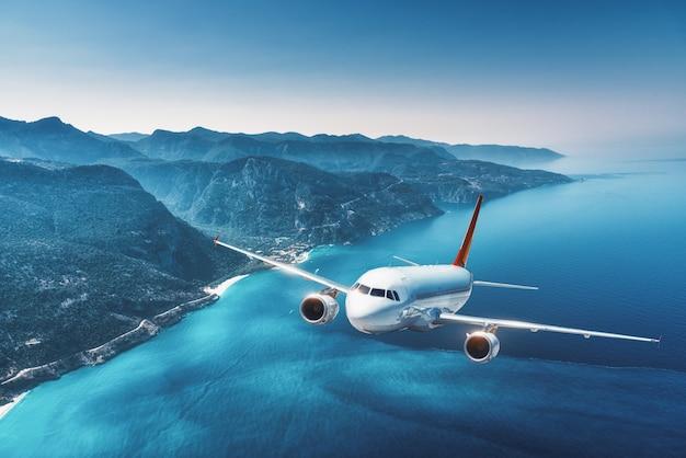 航空機は夏の日の出で島と海の上を飛んでいます。白い旅客機のある風景