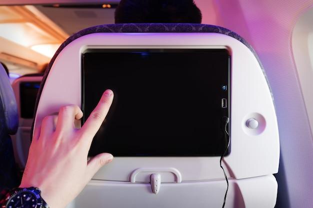 Самолет контролирует пассажирское сиденье. внутренний самолет. сенсорный экран. мужской палец нажимает на экран. пустая форма для дизайна. пустой экран. развлечения во время полета