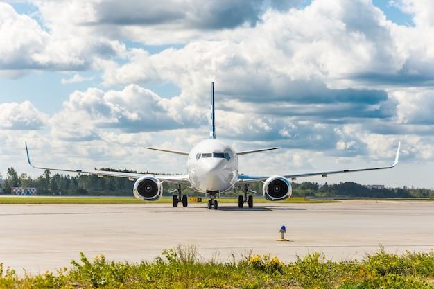 구름 속의 그림 같은 하늘을 배경으로 정확히 프레임 중앙에 있는 공항의 조향 트랙에 있는 항공기.