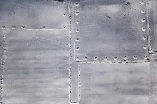 Кожа самолета крупным планом. заклепки на сером металле.