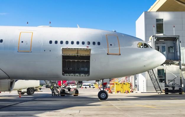 공항 주차장에 서 있는 항공기는 승객의 짐을 실을 준비가 되어 있습니다.