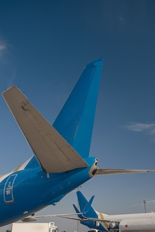背景に青い空と空港の国際航空会社の航空機の尾翼。飛行機、輸送の概念