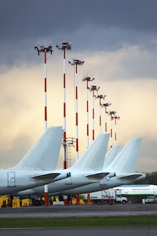 Aircraft tails parked at airport apron against a cloudy sky.