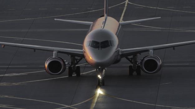 해질녘에 공항에서 활주하는 항공기