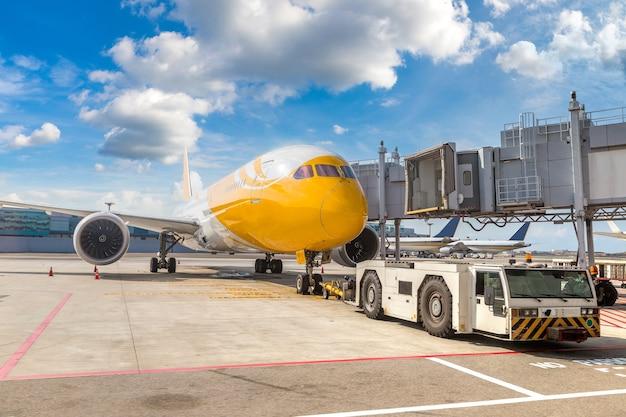Тягач самолетов и самолет в аэропорту сингапура чанги