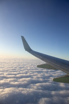 雲の上の高高度で空に航空機の翼