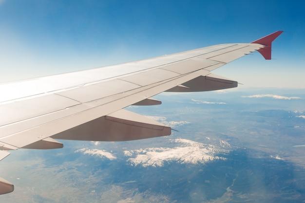 Крыло самолета на облаках, летит в горах