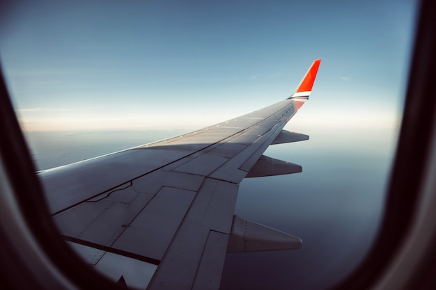Aircraft wing in the sunset light. airplane wing against the blue sky from the porthole. view from the airplane porthole to the clouds.