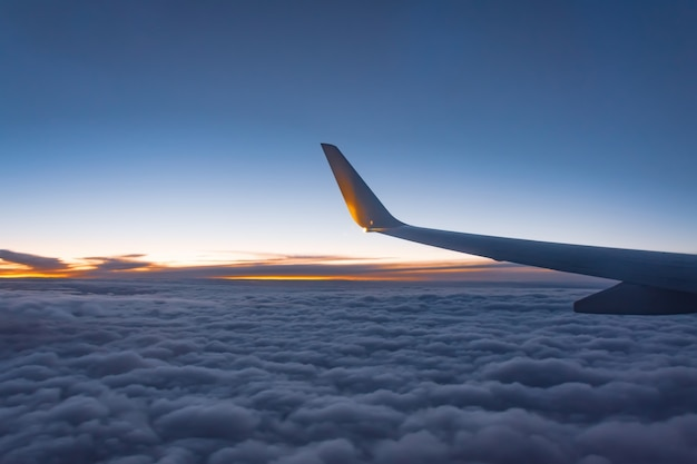 Aircraft wing view from airplane with cloudscape sky after sunset.