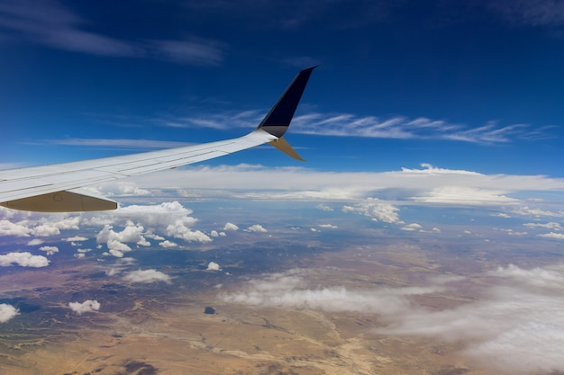 Aircraft in wing above white clouds in the sky of airplane