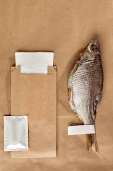 Вяленая плотва на крафт-бумаге с упаковочным пакетом влажной салфеткой и бумажной салфеткой