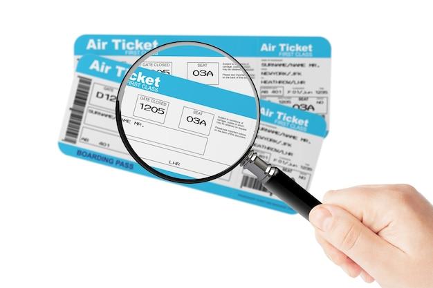 白い背景の上の拡大鏡のガラスを手に航空会社の搭乗券チケット